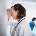 Depressed doctor leaning against wall at hospital corridor